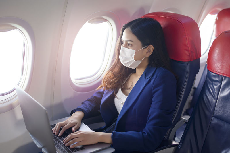 Young woman using mobile phone while sitting in airplane