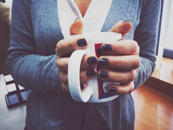 Close-up of human hand holding coffee cup