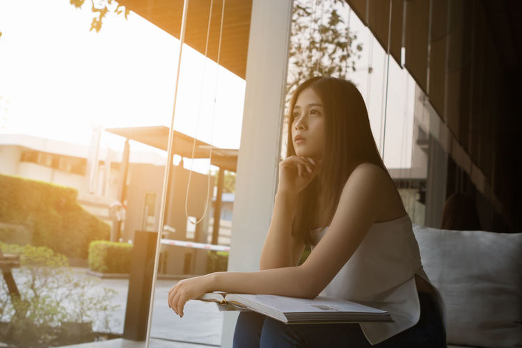 Thoughtful young woman looking through window