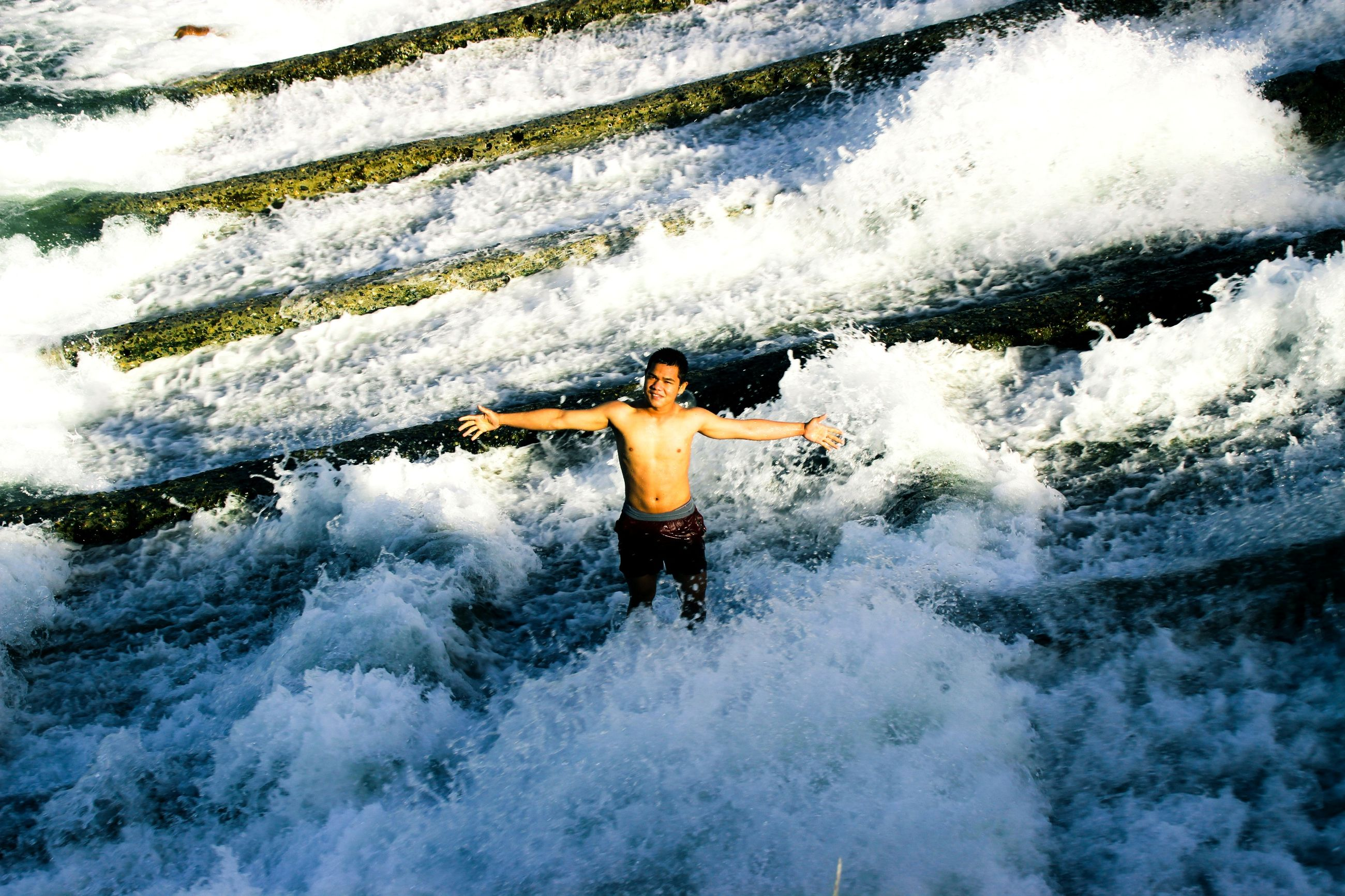 water, lifestyles, full length, leisure activity, season, winter, weather, standing, motion, cold temperature, high angle view, snow, splashing, enjoyment, surf, arms outstretched, waterfront, person