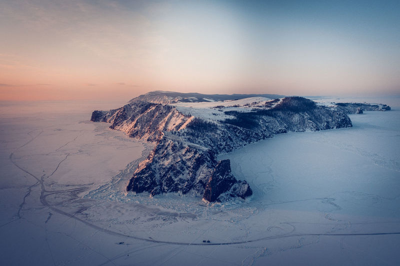 Aerial view of snow covered land against sky during sunset