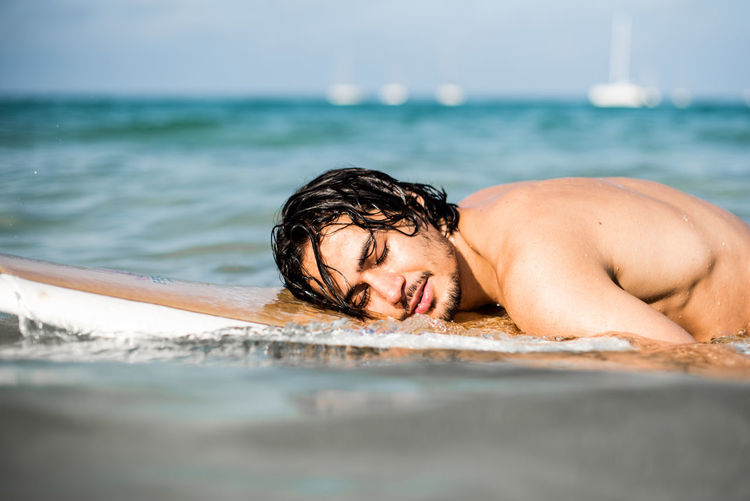 Portrait of shirtless young man in sea