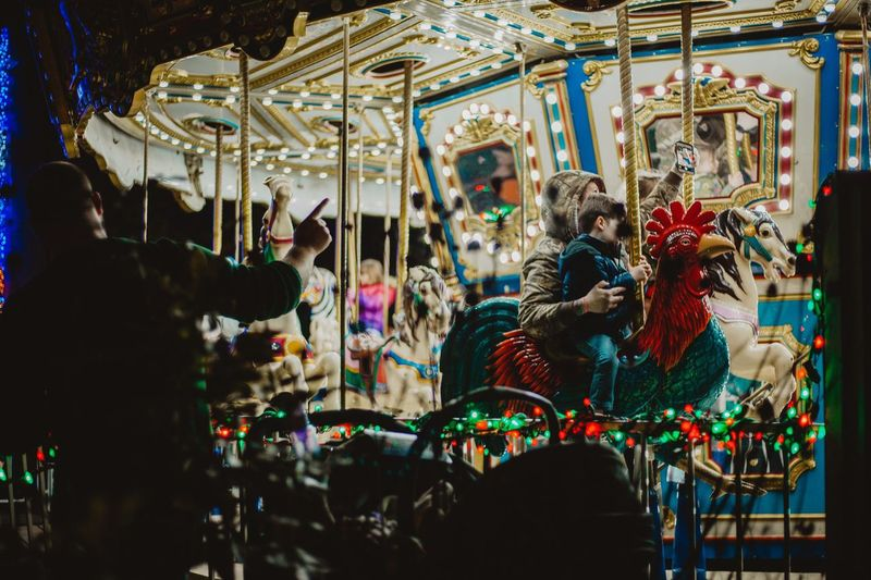 Mother taking selfie with son while sitting in carousel at amusement park during night