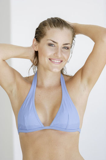 Portrait Of Smiling Young Woman In Blue Bikini
