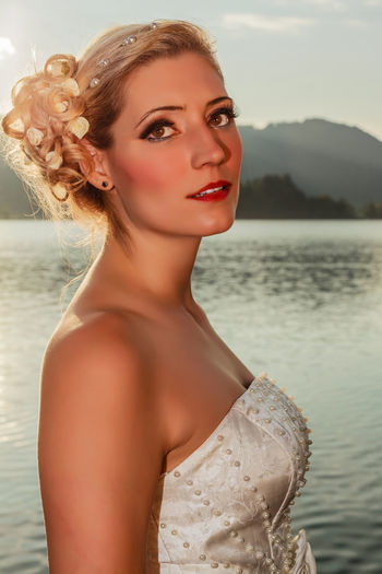 Portrait of a beautiful young blond woman in wedding dress on a lake. Fashion Beautiful Woman Beauty Beauty In Nature Beauty In Nature Blond Bride Ceremony Close-up Day Focus On Foreground Hairstyle Lifestyles Looking At Camera Marriage  Nature One Person Outdoors People Portrait Real People Sea Water Young Adult Young Women