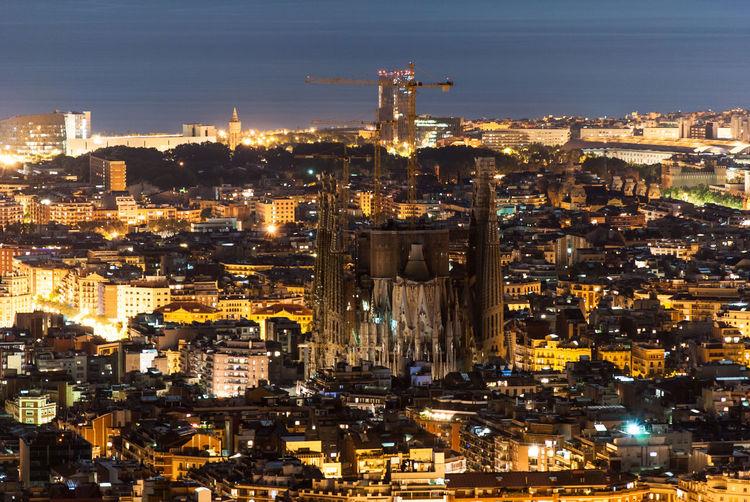 Sagrada Familia Amidst Illuminated Cityscape At Night
