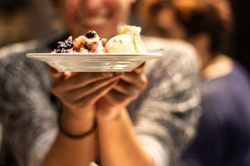 Midsection of person holding food in plate