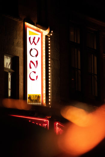 Close-up of illuminated sign on city at night
