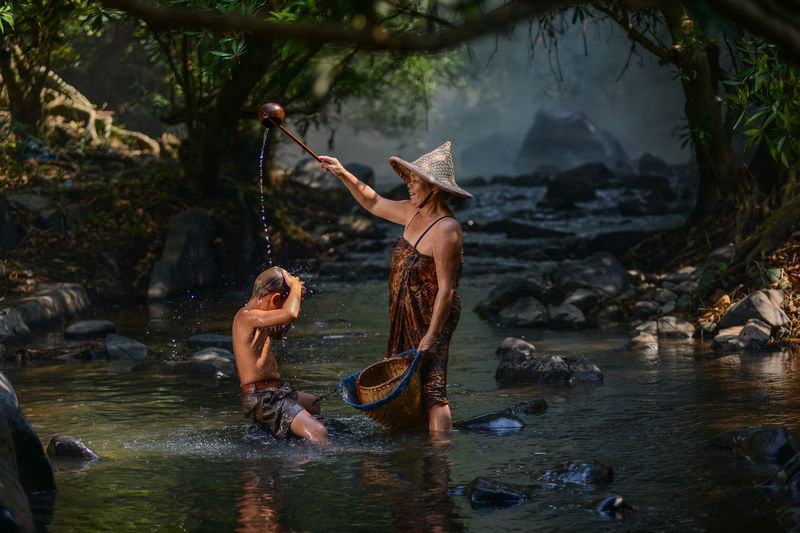 Side view of grandmother bathing grandson in river at forest