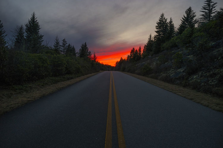 Country Road Amidst Trees Against Cloudy Sky During Sunset