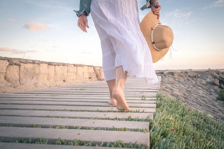 Low section of woman walking on boardwalk against sky