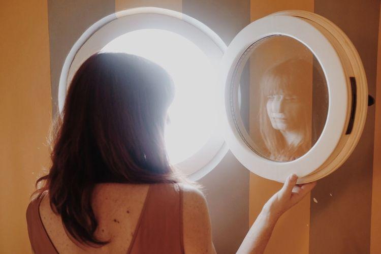 Rear View Of Woman Opening Circular Window