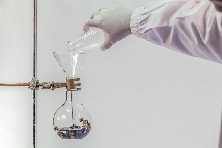Cropped Hand Of Scientist Experimenting Against White Background