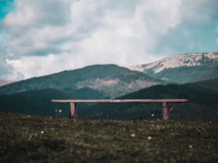Empty bench on land against sky