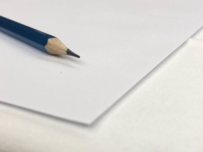 A sharpen pencil put on a corner of plain paper over the white desktop. EyeEm Selects Writing Instrument Pencil Still Life No People Indoors  Paper Education Close-up High Angle View Office Art And Craft Office Supply White Background White Color Sharp Wood - Material Copy Space Simplicity