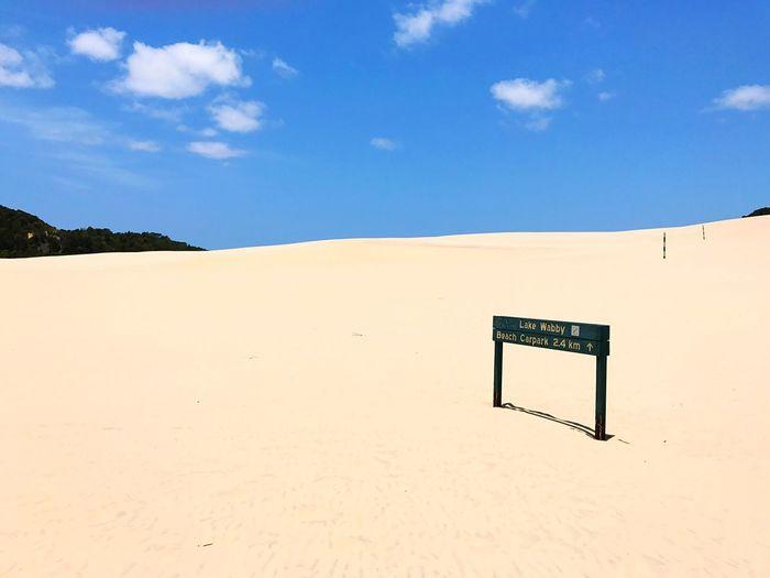 Sand dune on beach against blue sky