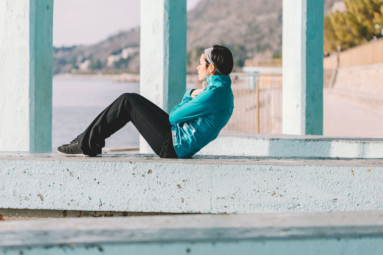 Side view of man sitting on wall