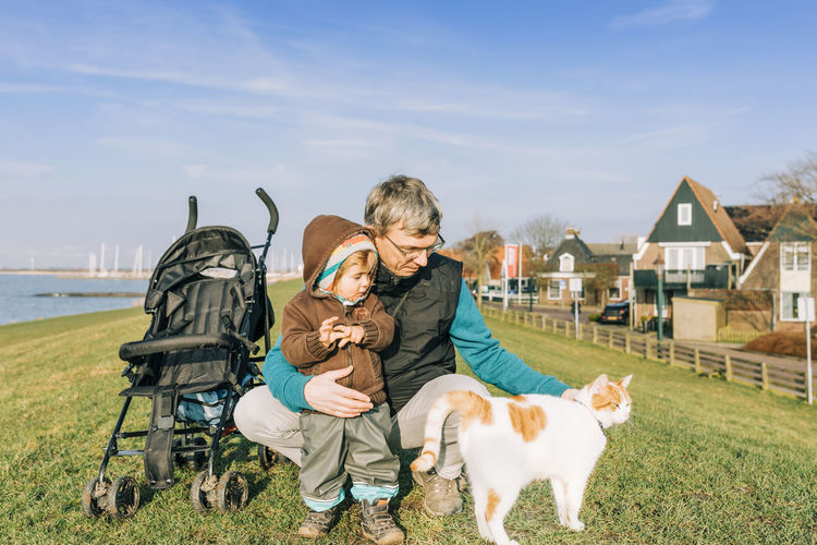 Toddler with grandfather and cat on dyke – Hindeloopen, Netherlands, Europe Adult Animal Baby Babyhood Boy Care Casual Cat Caucasian Child Childhood Close-up Connection Crouching Dyke  Family Feline Friesland Full Length Girl Grandchild Granddaughter Grandfather Grandparent Grass Happy Hindeloopen Holding Kid Lake Love Man Mature Nature Netherlands Outdoors People Pet Playing Portrait Sea Standing Stroking Sunny Tabby Tickling Toddler  Togetherness Vacations Water Domestic Domestic Animals Mammal Pets One Animal Real People Males  Men Lifestyles Leisure Activity Pet Owner
