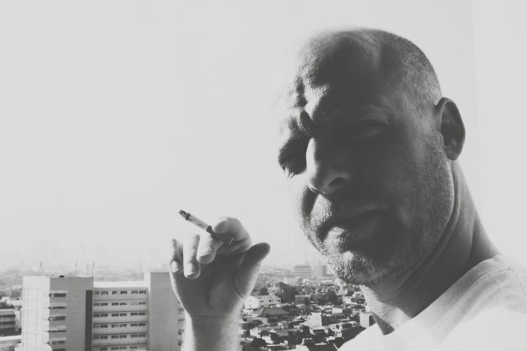 Close-up portrait of man smoking cigarette against city on sunny day