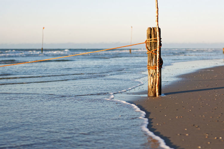 Wooden Posts by the Sea Sea Seascpae Ocean Strand Beauty In Nature Wood Wood - Material Wooden Post Holz Coast Coastline Küste Sand Beach Horizon Over Water Outdoors Landscape Landschaft Makro Fine Art Photography Rope