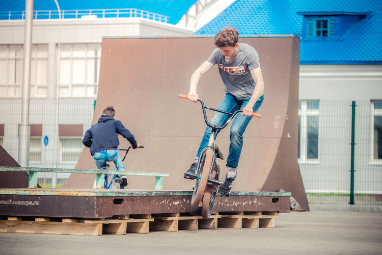 Friends Riding Bicycles At Playground In City