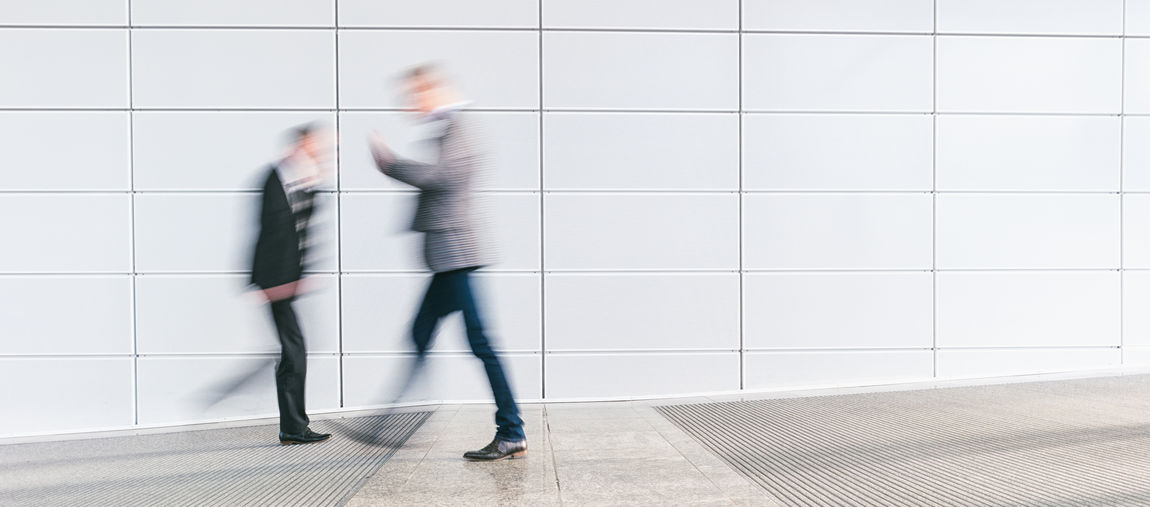 Blurred Motion On People Walking By Wall