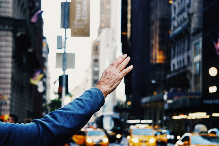 Cropped hand of man hailing taxi in city