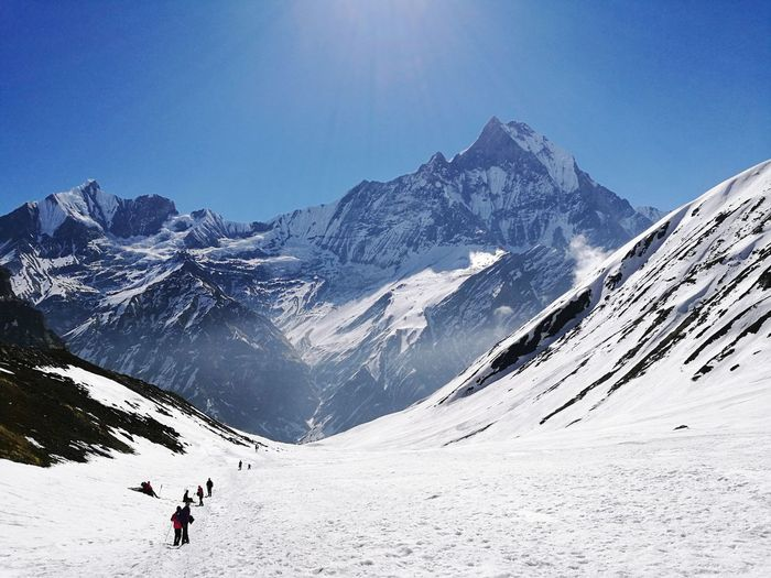 High Angle View Of Trekkers By Mountain Against Sky