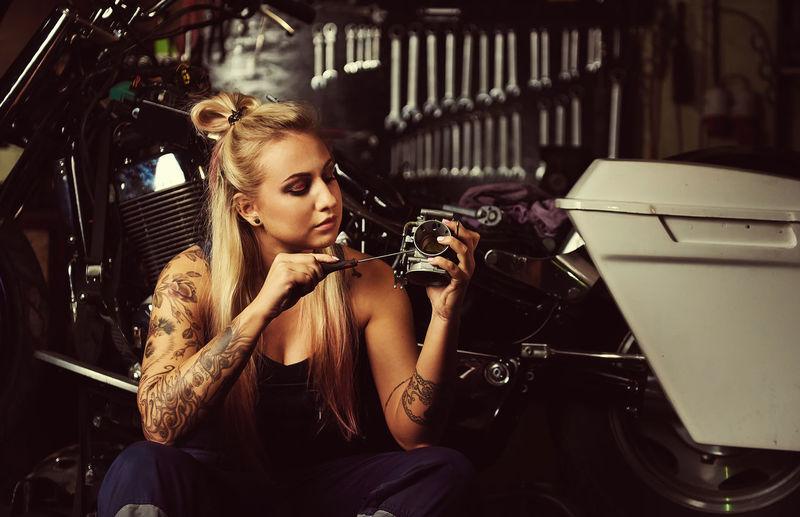 Woman repairing motorcycle at workshop