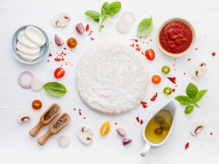 High angle view of dough and ingredients on table