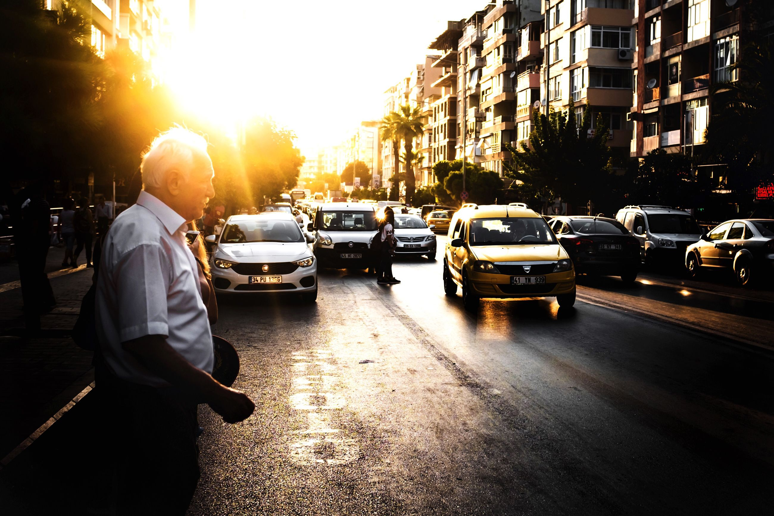building exterior, car, architecture, city, built structure, real people, land vehicle, street, outdoors, sunlight, sunset, men, day, sky, people