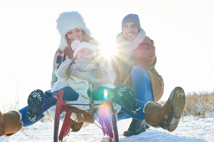 Happy friends sitting on snow covered land