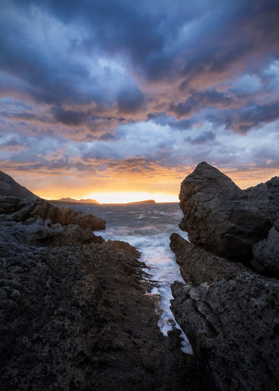 Rock formation on sea against sky during sunset