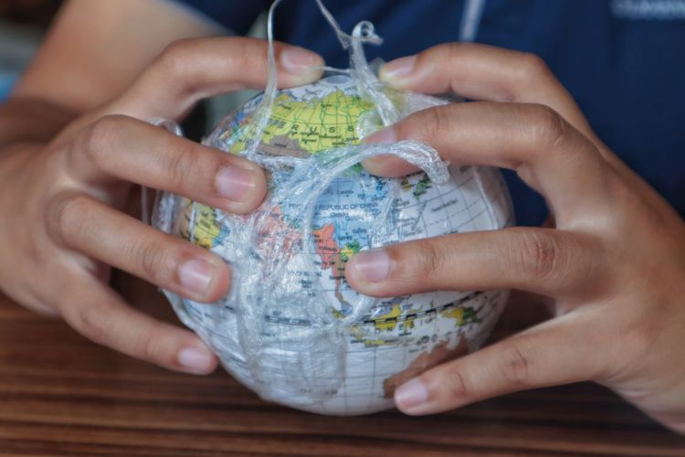 Midsection of woman holding globe in plastic on table