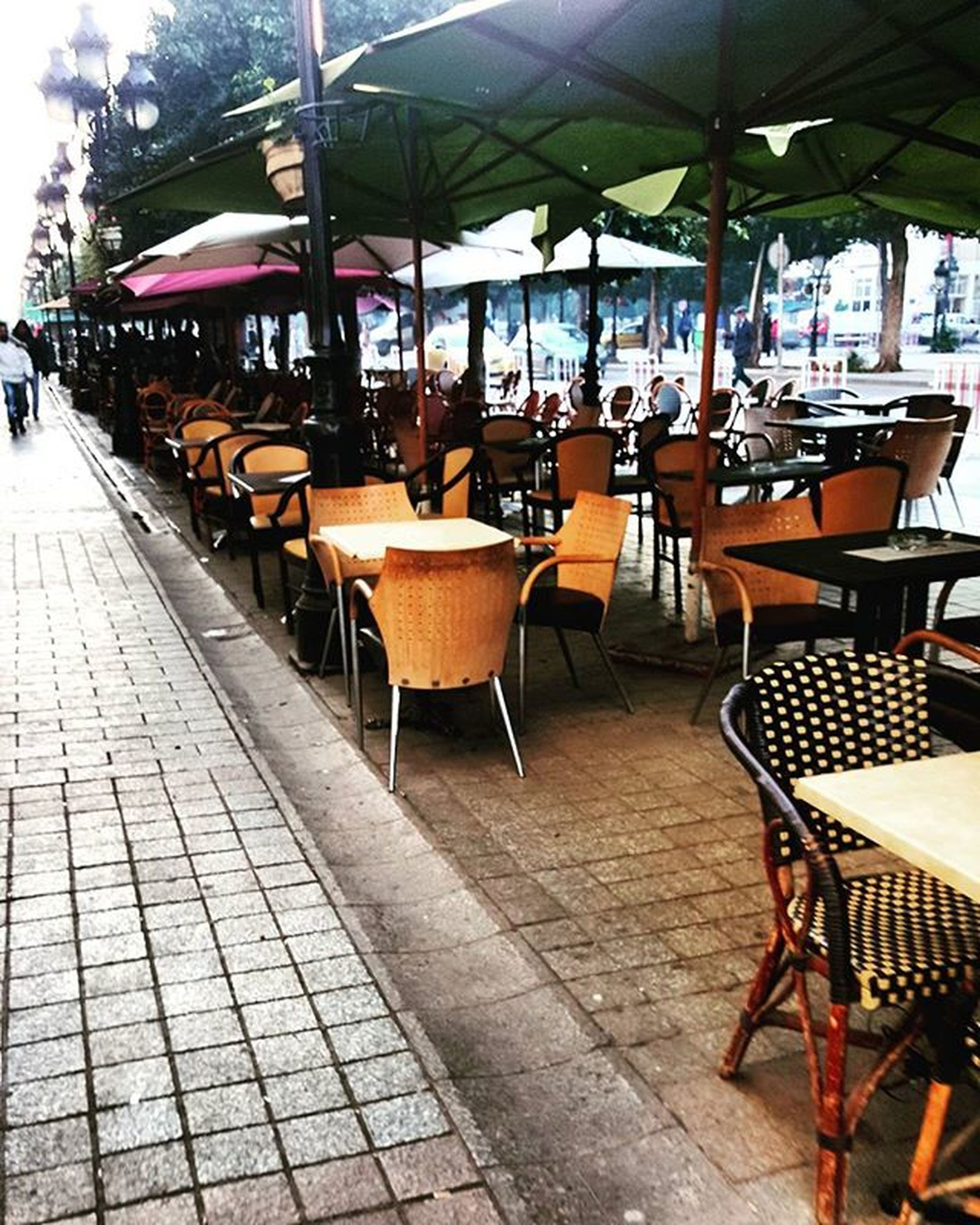 chair, table, restaurant, sidewalk cafe, empty, cafe, absence, incidental people, indoors, place setting, architecture, built structure, arrangement, seat, in a row, food and drink industry, sunlight, day, furniture, building exterior
