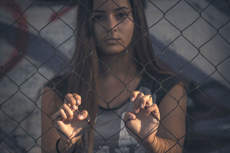 Portrait Of Woman Looking Through Chainlink Fence