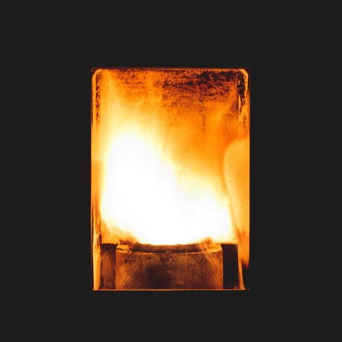 Close-up of burning candle against black background