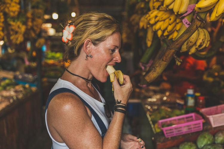 Side View Of Mature Woman Eating Banana At Market During Night