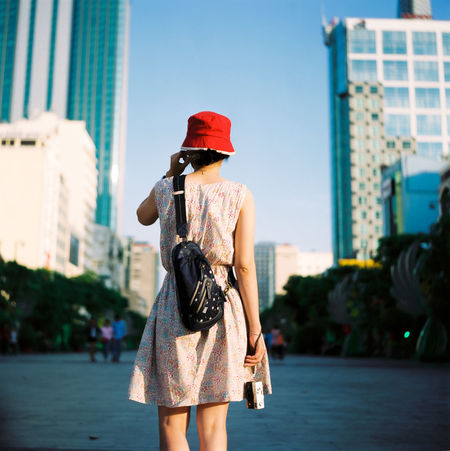A cropped image of woman walking in residential district- downtown of a city with many high rises during sunset Bucket Hat Building Capital Cities  Casual Clothing District Downtown Dress Enjoyment Fashionable Floral Flower Girl Hat Lifestyles Portrait Real People Red Lips Skyscraper Sunset Trendy Walking Woman Young Young Adult Young Women