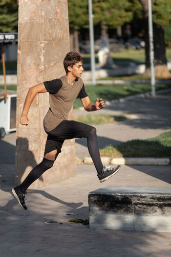Full length side view of young man running on footpath