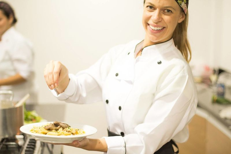 Portrait Of Happy Female Chef Garnishing Pasta In Plate At Commercial Kitchen