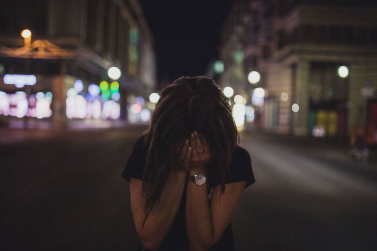 Terrified woman covering face while standing on street at night