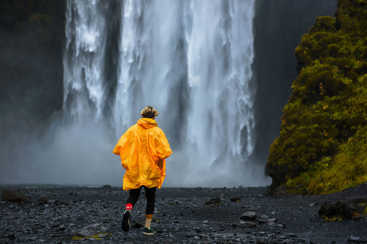 Rear view of person standing on rock against waterfall