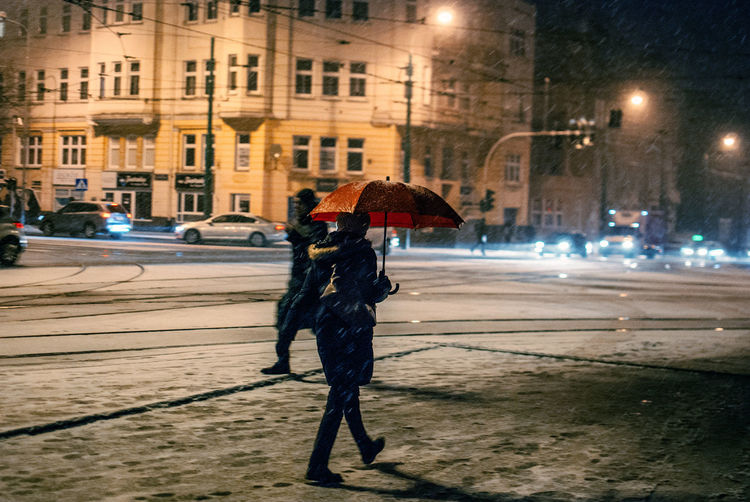 Rear View Of Woman Carrying Umbrella During Snowfall In City At Night