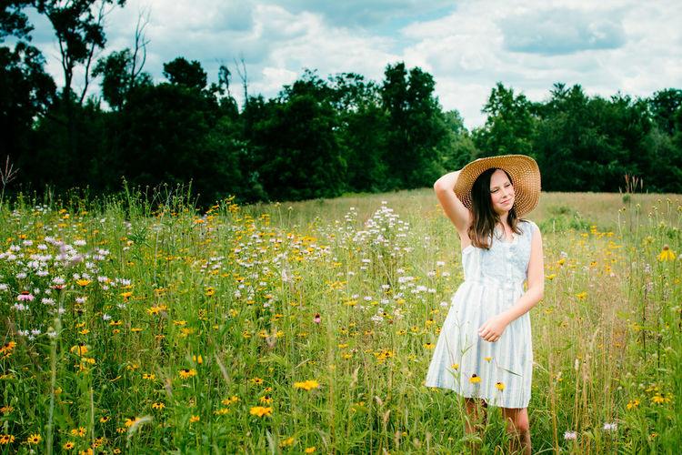 Woman standing by flowering plants in a field