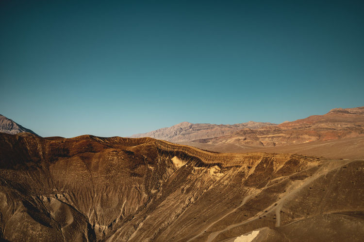 Wide angle shot of the Ubehebe Crater volcanic landscape, Death Valley National Park, USA. Submitted to the Stay Out mission: A perfect Stay Out moment because this landscape is so inspiring that I just want to walk through and immerse in it. To capture these moments feels very essential to me - I want to share my view with the world and hope the atmosphere is perceptible. Stay Out Eroded Formation Outdoors Nature Desert Mountain Range Landscape Scenics - Nature Mountain Sky Clear Sky Ubehebe Crater Death Valley Death Valley National Park Volcano Volcanic Landscape Volcanic  Crater Volcanic Crater Extreme Terrain Desert Landscape Wide Angle High Resolution California USA My Best Photo Adventure Travel Destinations Travel Hiking Morning Sunlight Iconic Landmark Places Discover  Vastness Dramatic Sedimentary Rock Rim Crater Rim Fanglomerate Gullies Erupted Rills Ridge Sediments Flows Trail