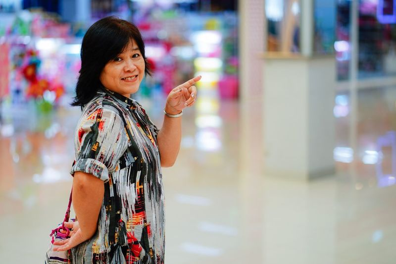 Portrait Of Woman Pointing While Standing In Mall