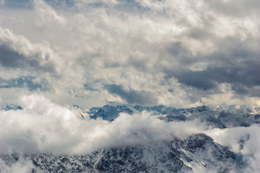 View to dramatic Clouds and snow capped smoky Mountains. Mountains Winter Berge 冬の景色 Glacier Backgrounds Weather Wintertime Ominous Above Atmosphere Climbing Cloud - Sky Cloudscape Day Dramatic Sky Environment High Up Idyllic Mountain Mountain Peak Mountain Range Nature No People Outdoors Scenics - Nature Sky Snow Tranquil Scene Wind