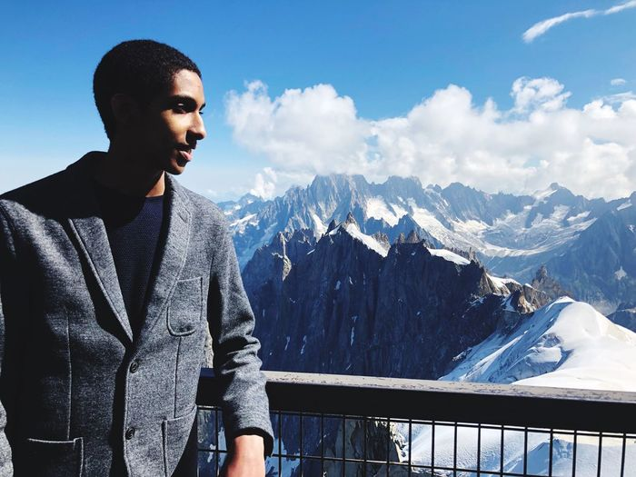 Young man standing by railing against snowcapped mountains and sky