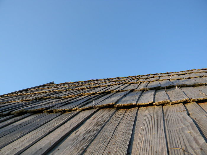 Low angle view of roof tiles against blue sky
